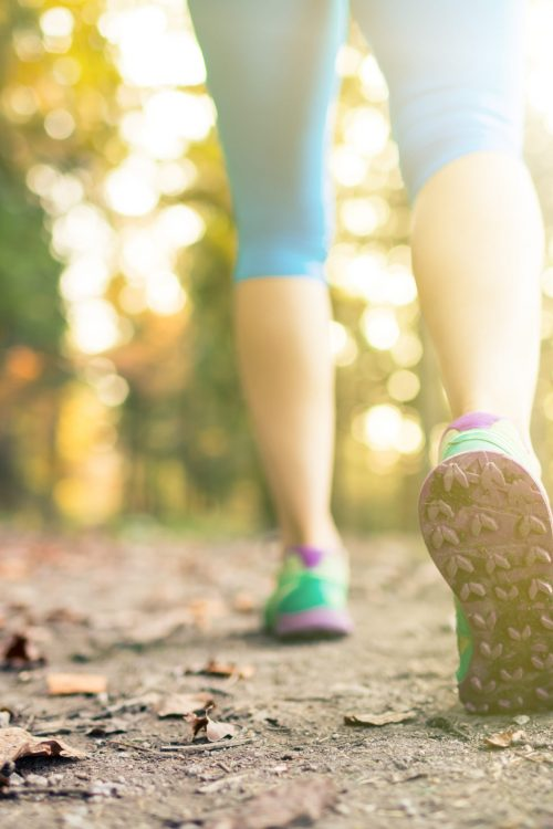 Woman walking and hiking in autumn forest, sport shoes. Jogging, trekking or training outside in autumn nature. Inspiring health and fitness concept.