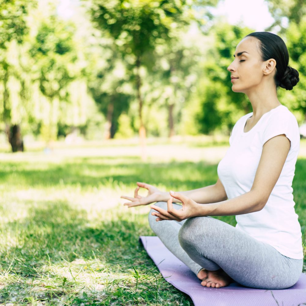 Female Yoga at park. Young brunette woman in lotus pose sitting on green grass in park. Concept of calm and meditation.